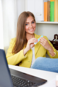 Beautiful young woman doing manicure in the office